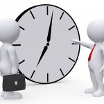 employer pointing at clock in front of employee